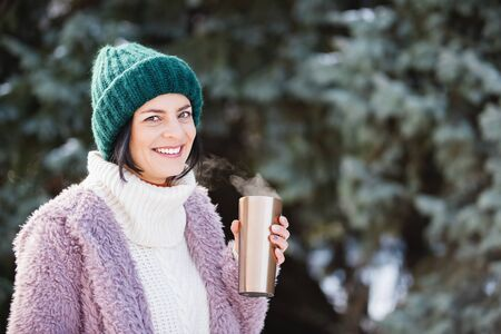 Young woman walking on winter day, holding travel stainless Steel mug with hot coffee. reusable water bottle. Refuse, reduce, recycle and zero waste concept. Ecology