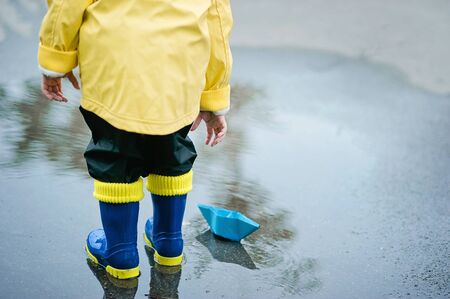 Little boy in raincoat and rubber boots playing in puddle. Happy little kid with paper ship by a puddle on warm summer day after rain. Active leisure for children. Child having fun outdoors. Stock Photo