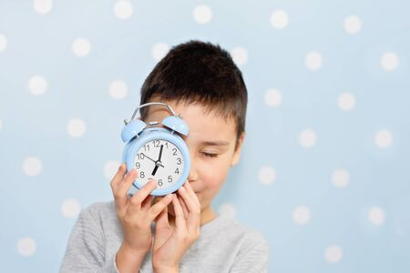 Cute little boy with alarm clock, People, school, time and lifestyle concept. sleepyhead or early bird. Sleeping child with alarm clock in front of face. Back to school. Copyspace