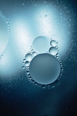 oil with bubbles on dark blue background. Abstract space background. Soft selective focus. macro of oil drops on water surface. copy space. air bubbles in water