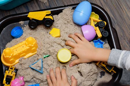 Child playing with kinetic sand and toy construction machinery. Hand of child in sand close up. Flat lay, top view. Indoor Table Game. Creativity Game concept. Activity for fine motor development Foto de archivo