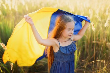 Girl blue and yellow flag of Ukraine in field. Ukraine's Independence Flag Day. Constitution day. 24 August. Patriotic holiday. Banco de Imagens