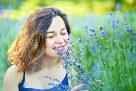 Beautiful girl in lavender field on sunset in France. Girl collect lavender. Series. Boho style clothing and jewelry. pregnancy outdoors. Maternity. pregnant woman with bouquet of lavender