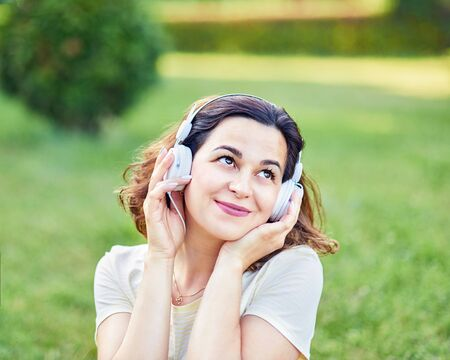 pregnant girl in headphones outdoors. Happy young pregnant woman sitting on carpet and listening music on headphones from smartphone at park. Pregancy, Relaxation and Health care concept. Online radio Standard-Bild
