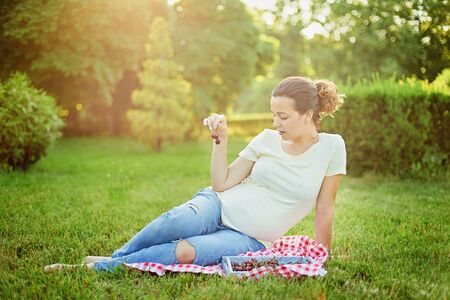 Pregnant woman hold cherries in garden. Concept for healthy food and pregnancy. Spring mood, enjoying nature, future mother relaxing and enjoying life in nature. Standard-Bild