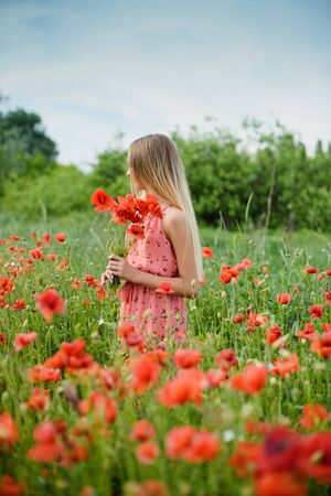 Ukrainian Beautiful girl in poppies field and wheat. outdoor portrait. Child collecting poppies and cornflower in summer field. Blooming Poppies memory symbol. no face