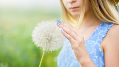 Summer portrait of girl with big dandelion. Close up photo of flower. Allergy free concept. Freedom