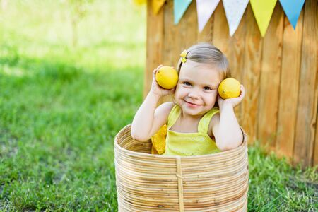 Little child girl with lemons at lemonade stand in park. Portrait of funny baby in basket with fruits. vitamins and healthy food. Useful citrus fruits as prevention of viral and respiratory diseases. Stockfoto