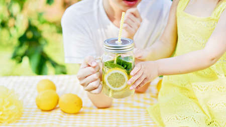 Children drink natural lemonade at stand in park. Summer refreshing natural drink lemonade. Detox fruit infused flavored water, cocktail in a beverage dispenser with fresh fruits