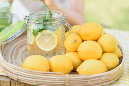 Plate with ripe fresh lemons and lemonade sassy water. Vitamins concept. copy space. Strengthening immunity concept. Tropical fruit. Organic citrus fruits for a healthy diet.