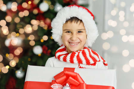 Happy excited child holding christmas gift box. Boy giving a Christmas present in decorated room. christmas and people concept. New Year Happy holidays. kid satisfied with present.