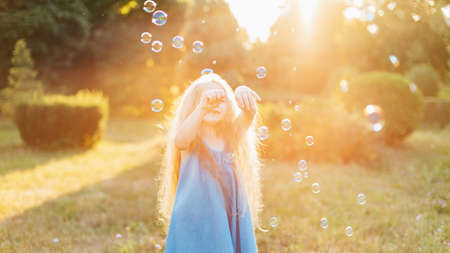 Child whirling, dancing plays on the meadow. Girl having fun with bubbles. Cute little longhair blonde girl dancing with soap bubbles at sunset park.