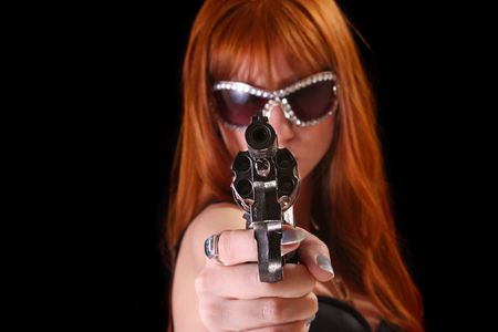 Young redhead woman with gun on black background photo