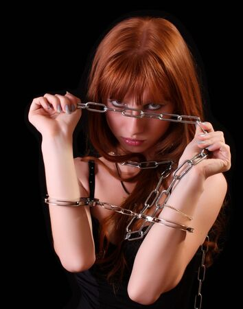 Young hot woman with handcuffs and chain on her hand on black background photo