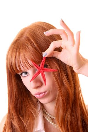 Young redhead woman with starfish in hand isolated photo