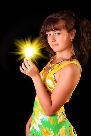 Young woman with bright lamp tube on black background photo