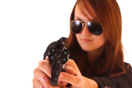 Woman in sunglasses aiming with revolver over white photo