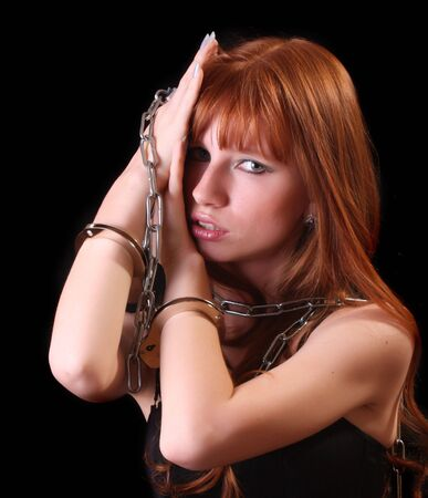 bound woman: Young hot woman with handcuffs and chain on her hand on black background Stock Photo