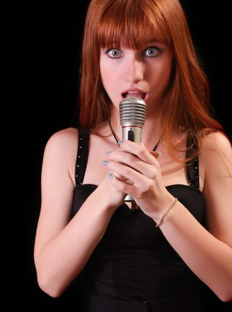 Young pretty woman singing with microphone on black background photo