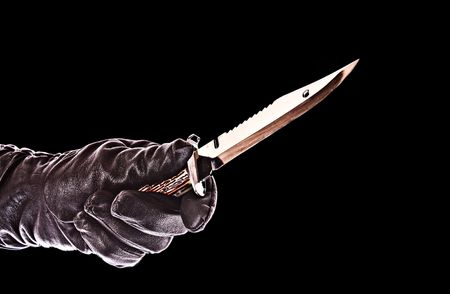 knife in black glove isolated on black photo