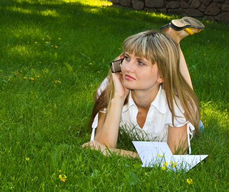 Girl speaking with telephone on grass photo