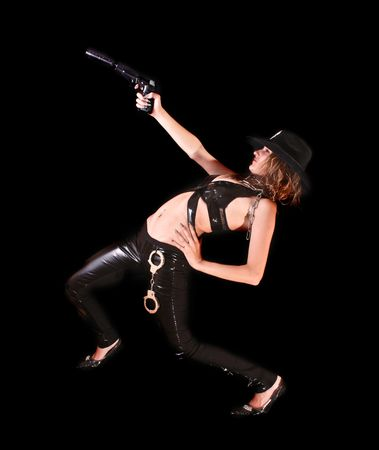 Beautiful woman aiming with gun on black background photo
