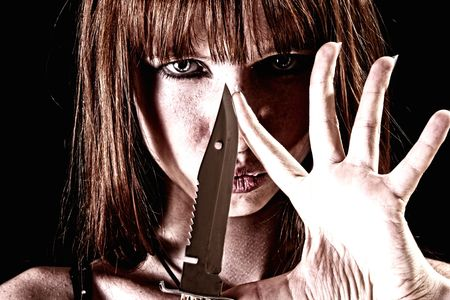 aggressor: Young woman with knife on black background