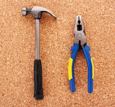 Hammer and pliers on cork board surface