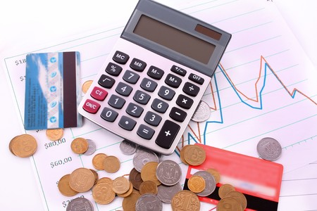 calculator , credit card and coins on chart background photo
