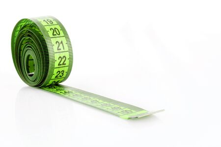 Twisted green measuring  tape isolated on white photo