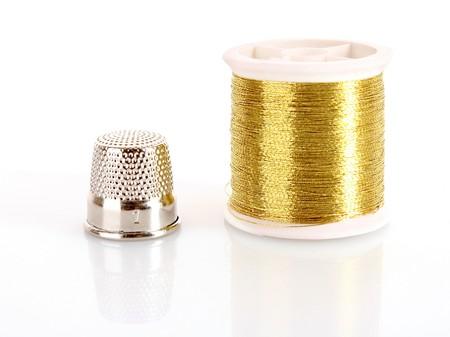bobina: Hilo dorado y dedal aislados en blanco