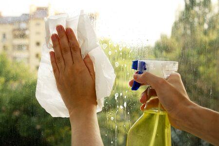 Hands spray clean the window photo