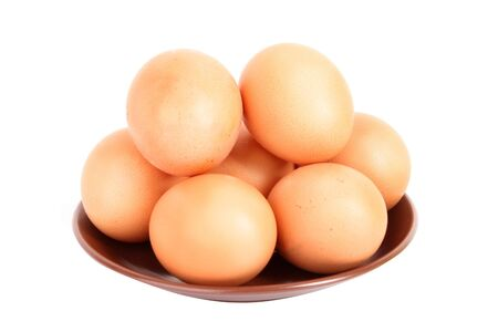 Grup of brown hens eggs in the plate isolated on white photo