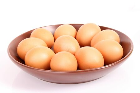 Group of brown hens eggs in the flat plate isolated on white photo