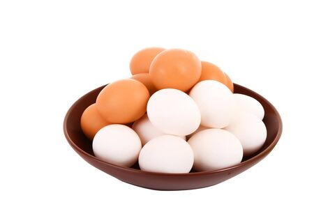 Group of brown and white hens eggs in the plate isolated on white photo