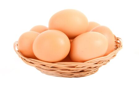 Group of brown hens eggs in the braided backet isolated in white photo
