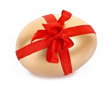 Golden egg with red stripe isolated on white photo
