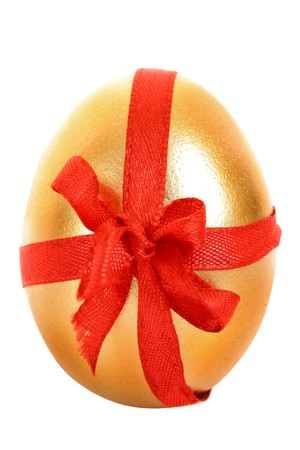 priceless: One golden hens egg with a red ribbon isolated on white