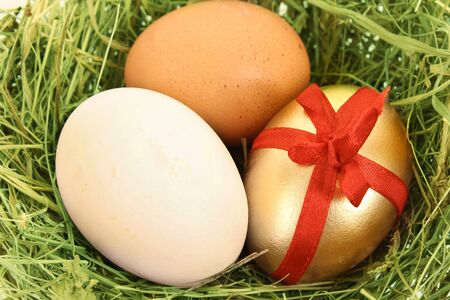 Brown,white and golden hens egg in the grassy nest on the wooden table photo