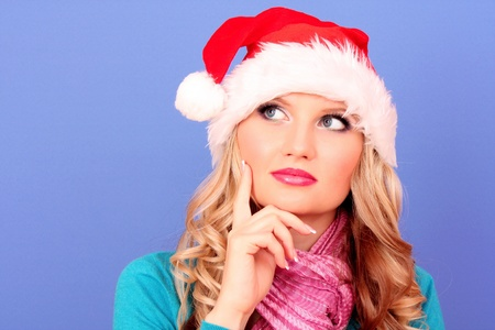 Beautiful christmas woman thinking in santa hat on blue background photo