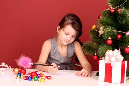 wishlist: Little girl writing wishlist on red background