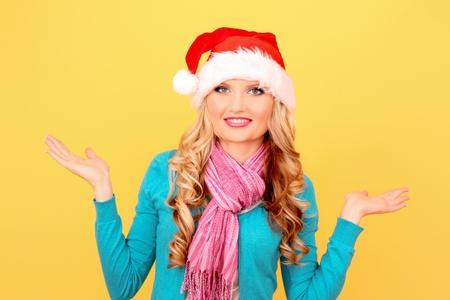 Beautiful christmas woman thinking in santa hat on yellow background photo