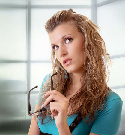 Young woman looking up with glasses in hand photo
