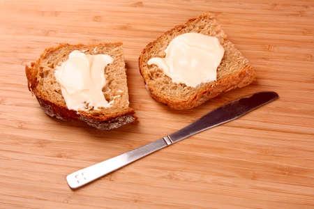 Kinfe und Brot mit Butter on wooden surface Standard-Bild