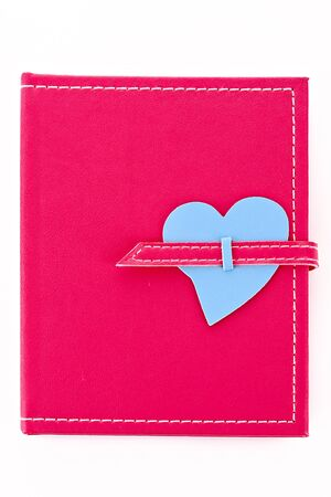Notebook with heart shape isolated on white photo