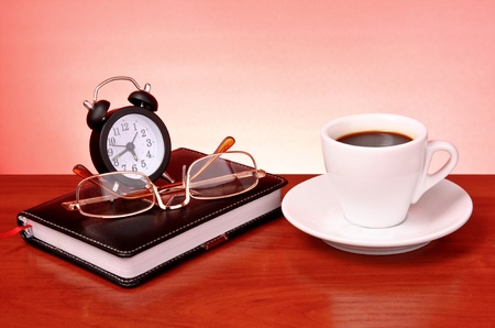 Cup of coffee, book, clock and calculator on wooden table photo
