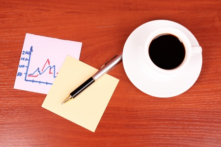 cup of coffee, a couple of stickers, chart and pen on table background photo