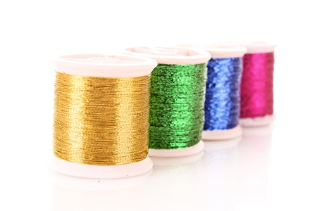 Pile of coloured bobbins of lurex thread isolated on white photo