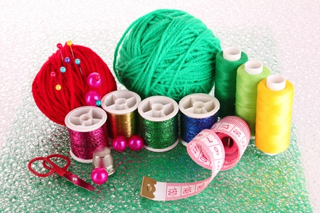 Coloured bobbins of threads, woolen balls and cushion for pins isolated on white photo