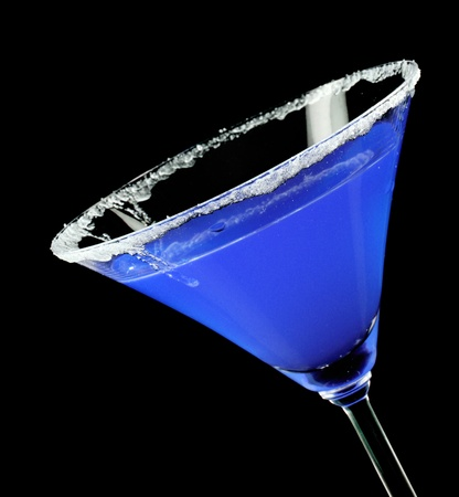 hard liquor: Martini glass with blue coctail on black background